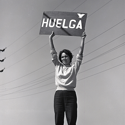 Dolores Huerta holds a 'Huelga' sign.