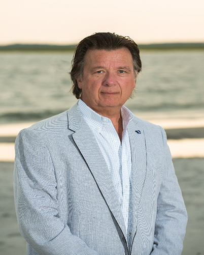 Man in suit on a beach.