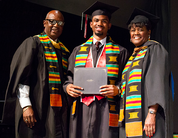 African American Male accepts certificate from faculty at the African American Pre-Commencement Ceremony.