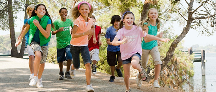 Group of diverse children running on a path