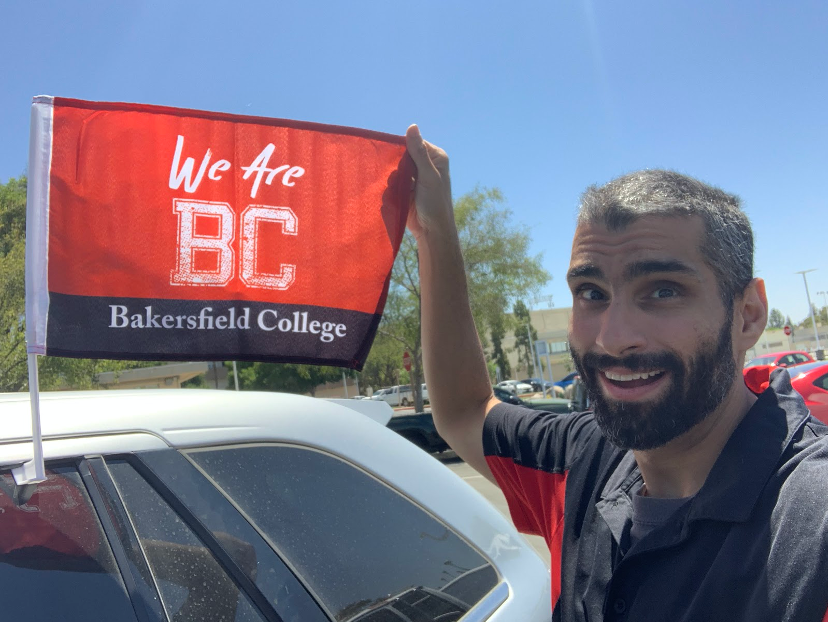 Nicky Damania holds out We Are BC flag attached to a car.