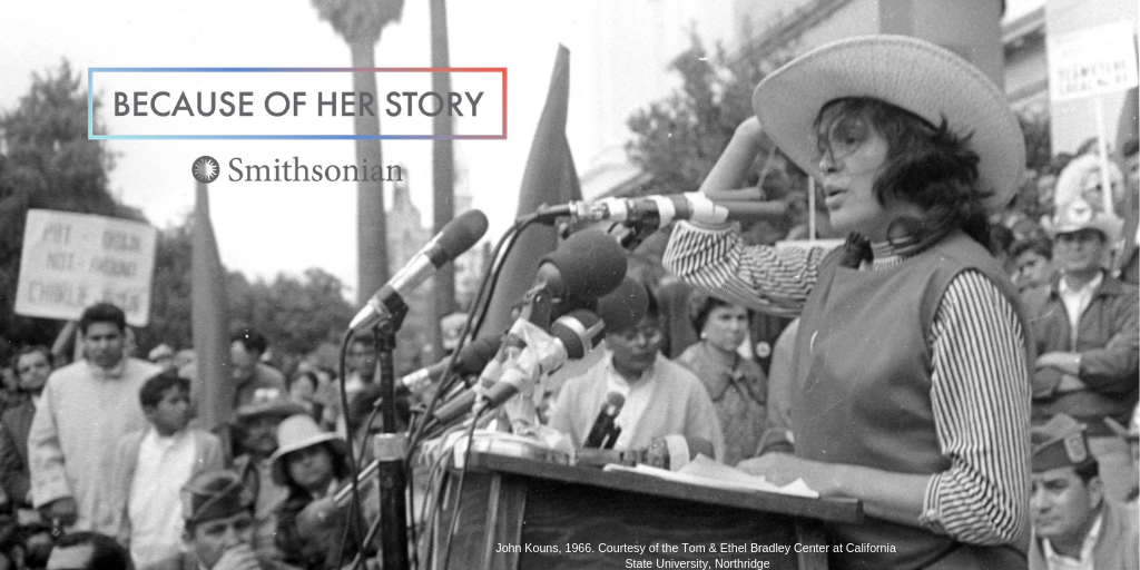 Because of Her Story, Smithsonian, Dolores speaks at a podium with microphones wearing a straw hat.
