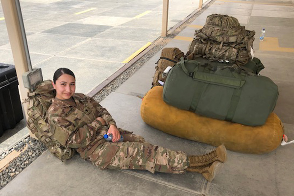 Female solider sitting on ground with luggage