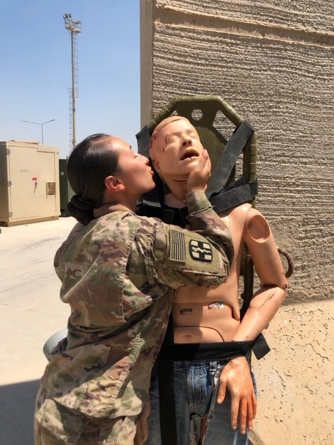 A soldier kisses an anatomy doll.