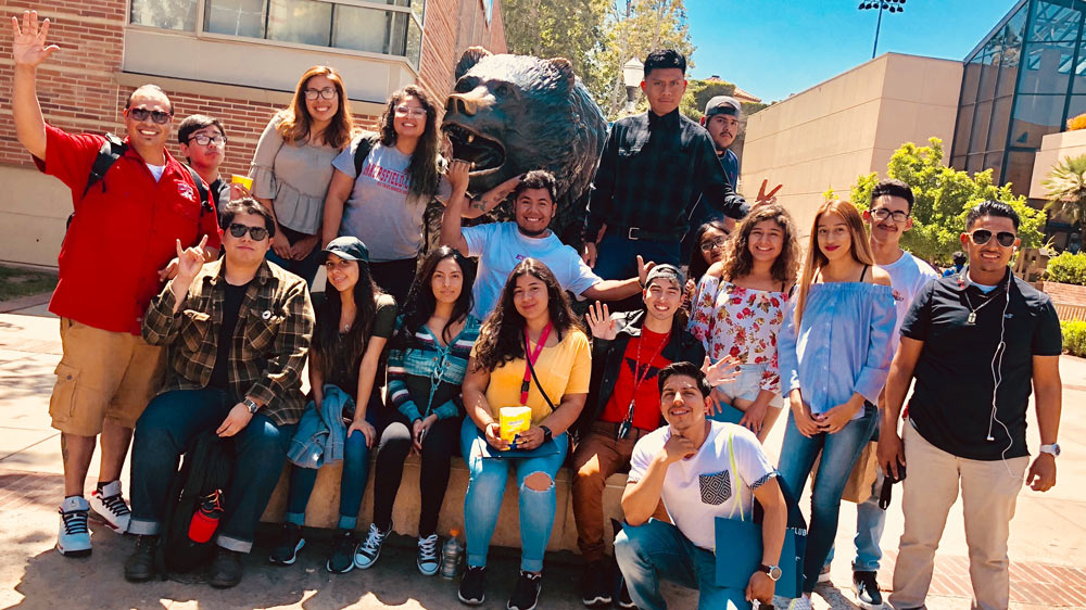 Group of students standing by bear statue