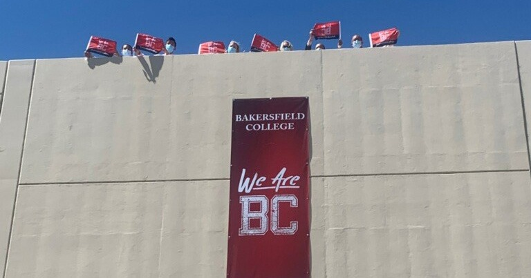 People with masks waving We are BC flags from top of building with We are BC; Congratulations Class of 2020 sign hanging.