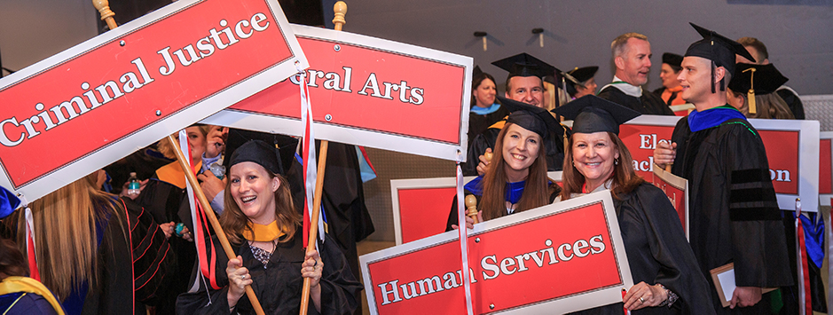 BC Faculty holding subject signs, Criminal Justice, Liberal Arts and Human services, in the processional.