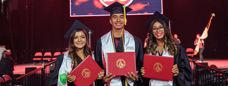 Three graduating Renegades hold their diplomas.