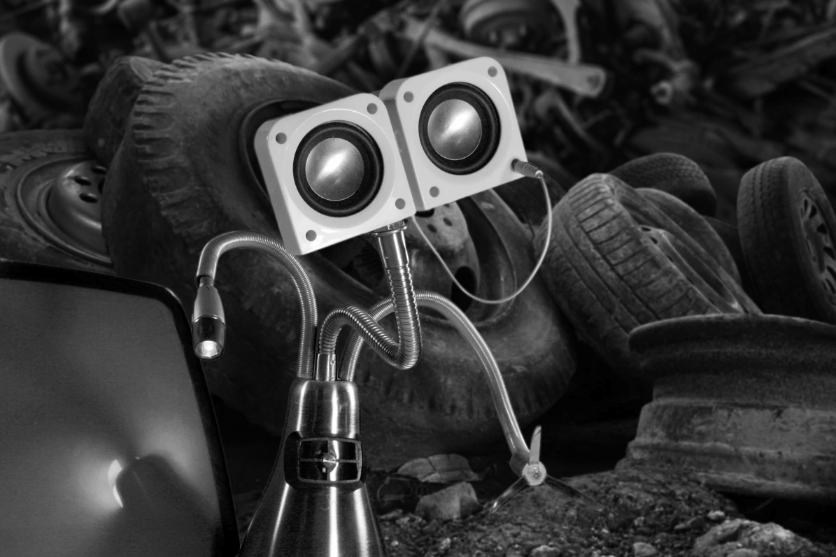 Black and white photo of speakers and lamps arranged in a junkyard so that they look like a face.