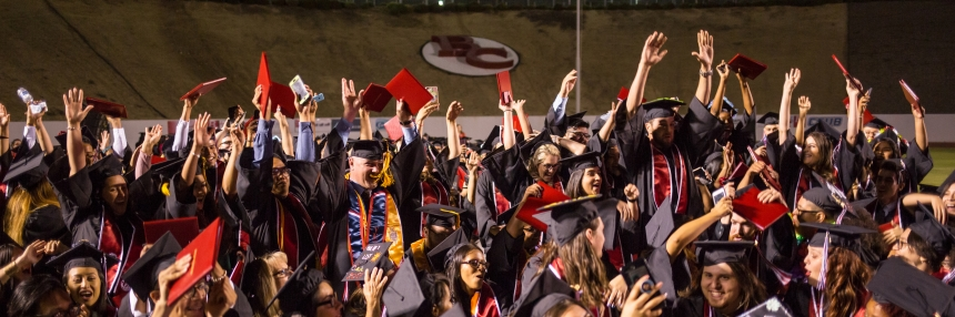 Graduates celebrate with hands in air.