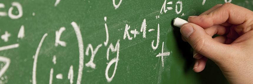 A hand writes mathematics equations on a chalkboard