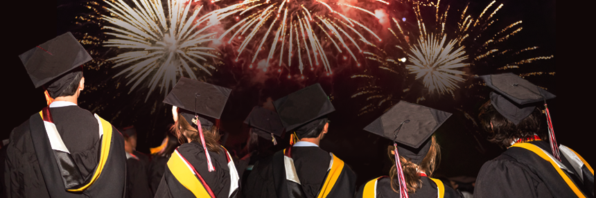 Graduates celebrate in front of fireworks