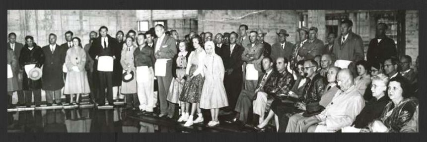 Black and white photo of gathering of people in the 1950's.