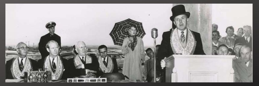 Man in top hat speaking with 4 more prestigious appearing men and a woman with umbrella, B&W, 1950's.