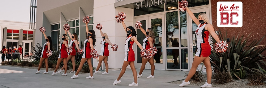 Cheerleaders dance with masks on in front of the Campus Center.