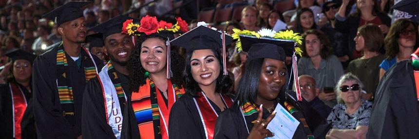 5 graduates in full regalia smiling.