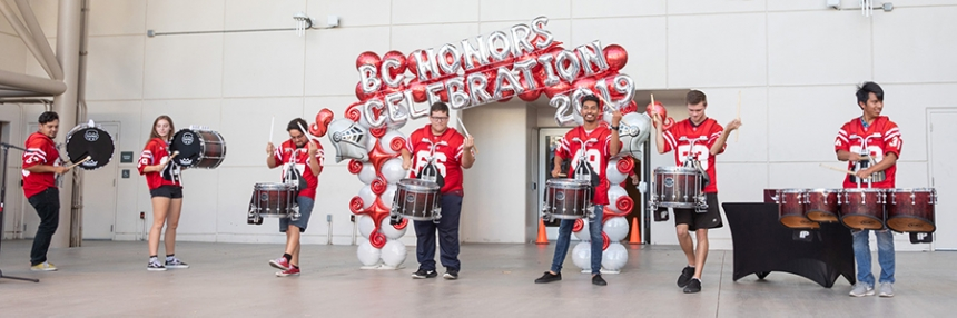 Drummers on stage in front of Honors Celebration balloons.