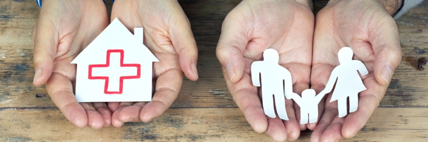Two hands holding paper cutouts of a house and family