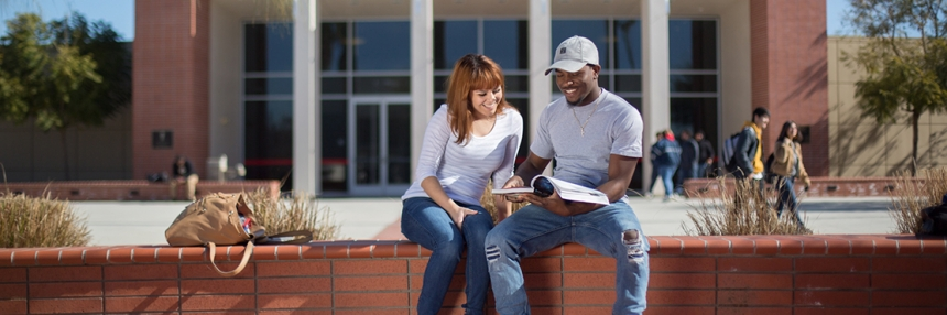 Two students study in front of indoor Theater.