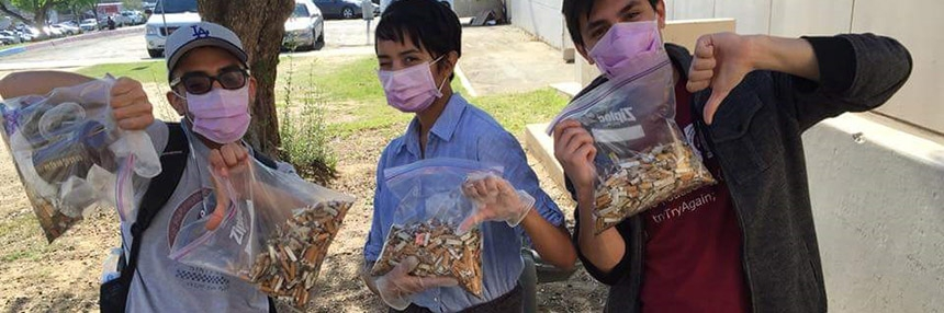 students pose with cigarette butts and surgical masks