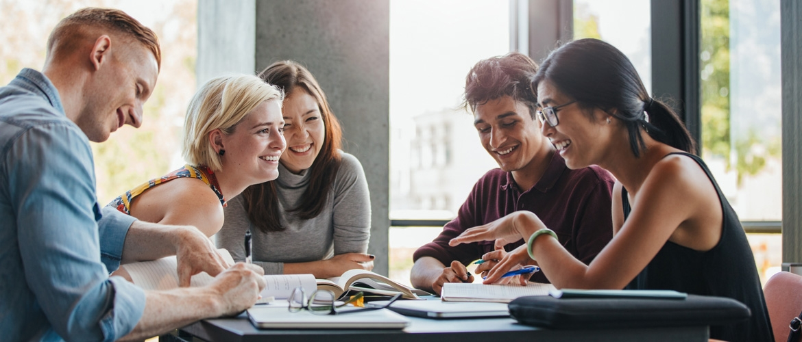 Five college students studying and smiling