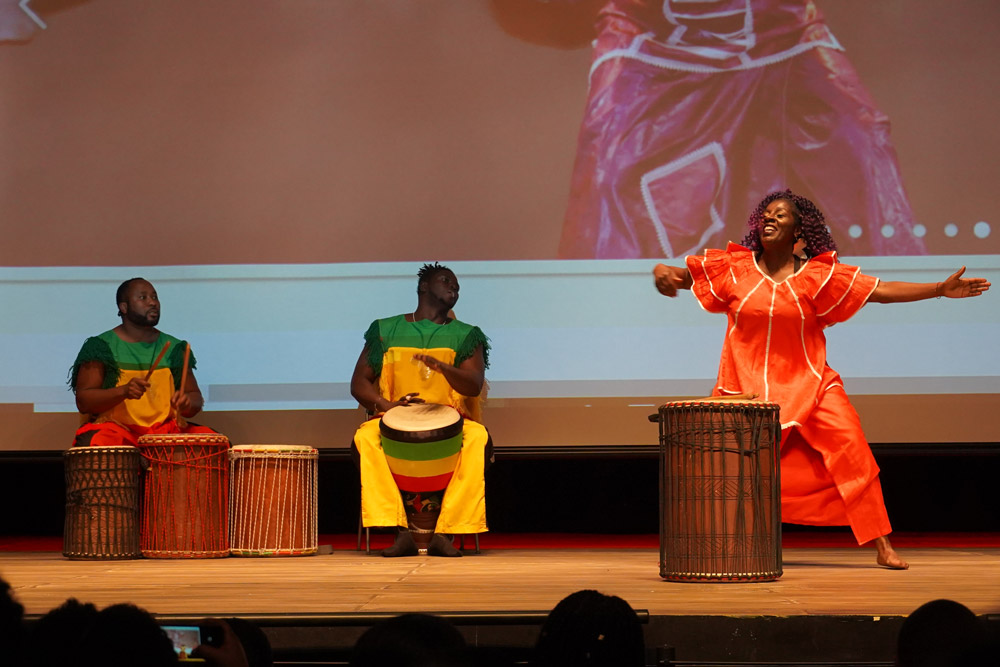 Three African Americans on stage playing drums
