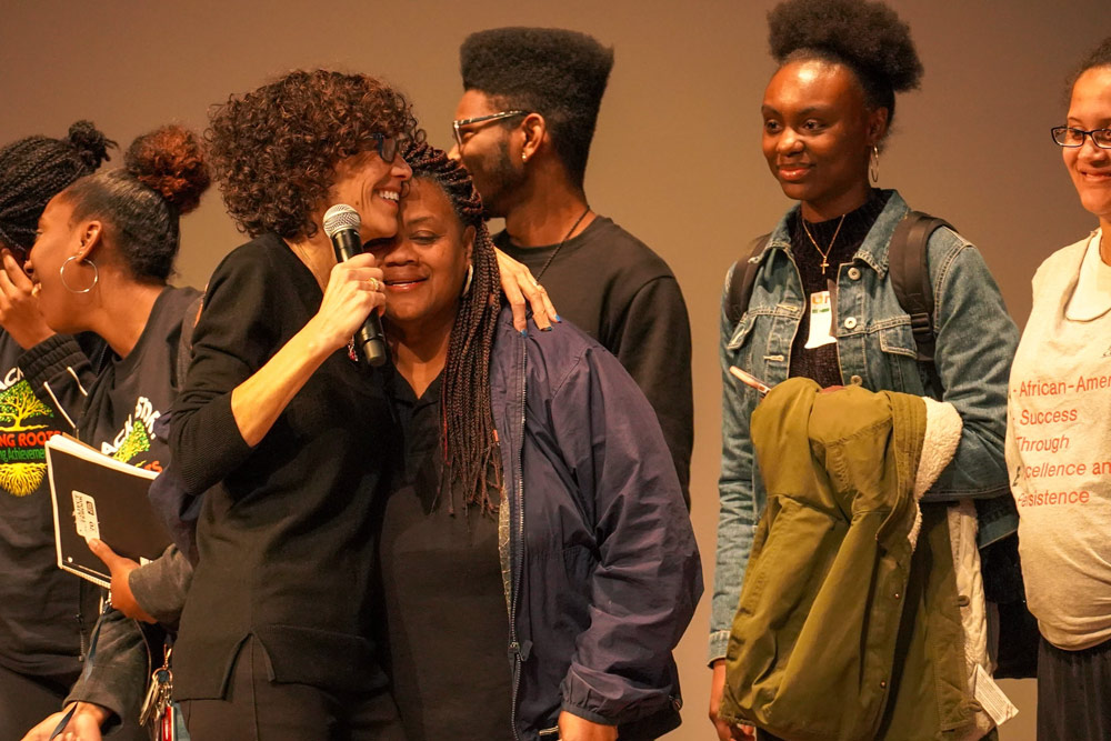 African American students on stage being hugged by woman