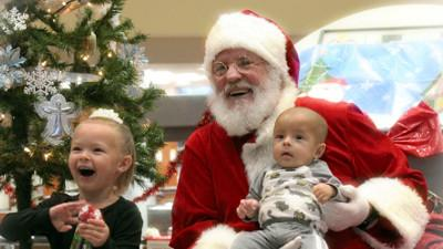 Santa cannot help but smile at the enthusiasm of little Haelyn Sullivan and her baby brother Holdyn Leuschen, children of Cerro Coso student Ariana Sullivan, during the 2018 Angel Tree event at the college.