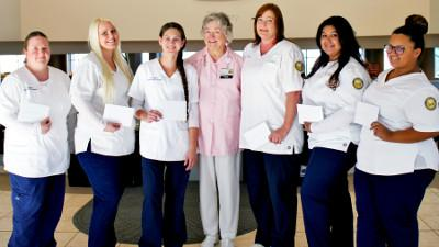 (L to R): Nursing students Alfie J. Mullins, Kourtney Pott, Kara Olson, Pink Ladies Scholarship Chairwoman Barbara Martin, Kimberly Tanner, Sonia Torres, and Briana Wright.
