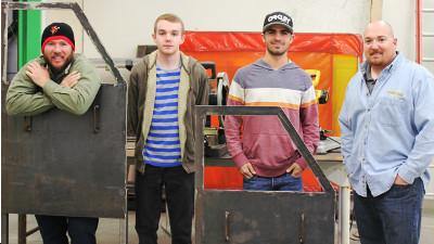 Welding students (l to r) Steven Payne, Nicholas Windsor, and Dustin Anderson pose for a picture of the steel doors they made with Instructor David Villicana.