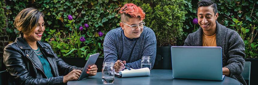 3 young adults outdoors studying with computers