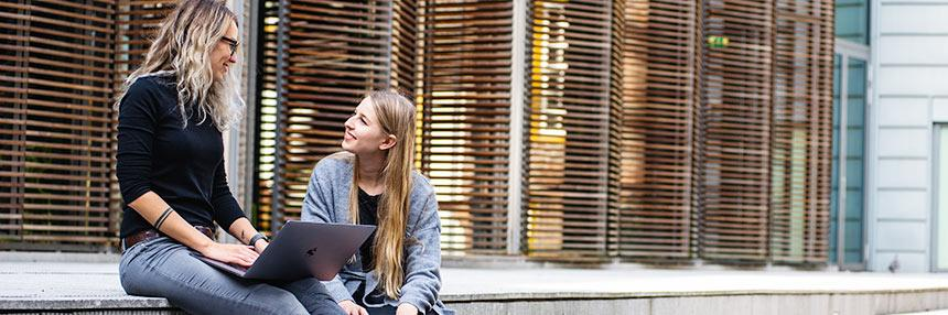 2 young adults sitting outside with laptop computer