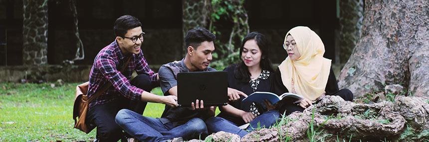 4 young adults outside studying with computers