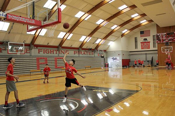 a boy performing a layup on the basketball court in the PC gym